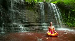 Meditating with Facial Painting in borneo rainforest waterfall - stock footage