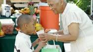 African American grandmother giving grandson orange juice Stock Footage