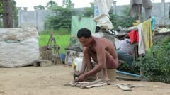 Father in slums preparing fire by cutting wood Stock Footage