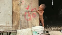 Naked baby crying in shack Stock Footage