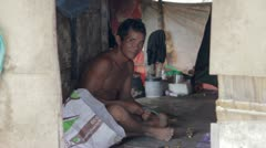 Adult man inside shack in a slum Stock Footage
