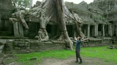 Happy man raising arms in mysterious preah khan temple, angkor - stock footage