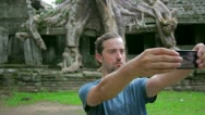 Stock Video Footage of visitor taking picture bizarre nature of preah khan temple, angkor