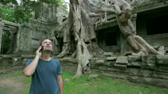 Young man talking phone in preah khan temple, angkor Stock Footage