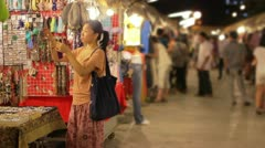 Chinese Young Woman Shopping at asian night market Stock Footage