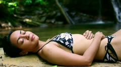 Sexy girl with bikini lying down in waterfall river Stock Footage