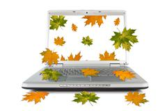 autumnal leaves falling out of computer - stock photo