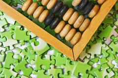Wooden abacus on pile of green puzzle Stock Photos