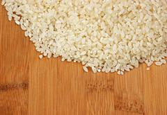 Raw rice and on bamboo board Stock Photos