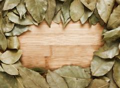 frame of dried bay leaf, a wooden board - stock photo