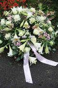 white sympathy flowers near a grave - stock photo