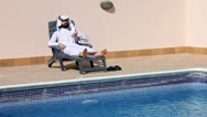 Stock Video Footage of saudi arabian man talking on phone at swimming pool