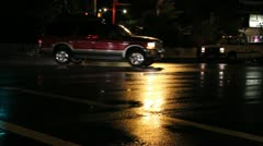 Suv's and trucks go through a rainy intersection at night - stock footage
