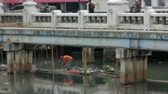 Indonesian man working in unhealthy open sewer of jakarta Stock Footage