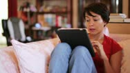 Girl touching tablet computer screen at home Stock Footage