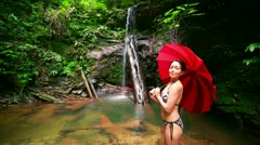 Girl with umbrella at waterfall in borneo rainforest Stock Footage