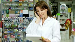 Young pharmacist talking on the phone with client Stock Footage