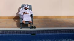 Saudi arabian man using his phone at swimming pool Stock Footage