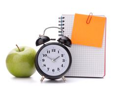 Alarm clock, blank notebook sheet and apple. Stock Photos
