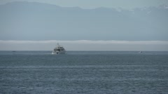 Motor Yacht out to sea, fog bank and mountains in bg, long shot Stock Footage