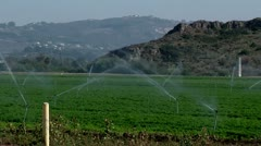Irrigation sprinklers watering field california water drought vegetables growing Stock Footage