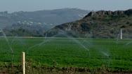 Irrigation sprinklers watering field california water drought vegetables growing Stock Footage