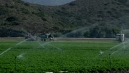 Irrigation sprinklers watering fields california water drought green produce Stock Footage