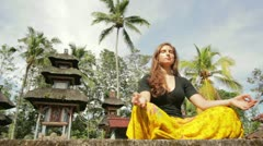 Caucasian woman meditating yoga in balinese temple Stock Footage