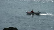 Man paddling his skiff along shore sunny day Stock Footage
