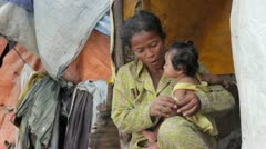 Mother feeding baby in cambodian slums, close to dump area Stock Footage
