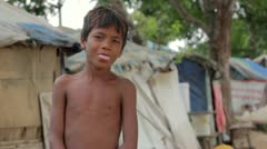 Stock Video Footage of Cambodian boy in slum, shacks at background