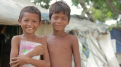 Cambodian boys in slum, shacks at background - stock footage