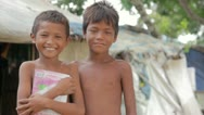 Stock Video Footage of Cambodian boys in slum, shacks at background