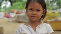 Cambodian girl in slums, garbages at background - stock footage