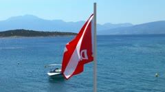 Waving Divers Alert Network (DAN) flag and Mirabello Bay near Agios Nikolaos Stock Footage