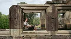 Caucasian tourist travel in baphuon temple looking camera, angkor, cambodia Stock Footage