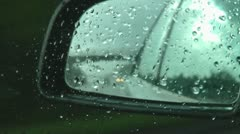 Looking into wing mirror of silver car travelling on motorway in the rain Stock Footage