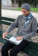 man writing on netbook on a bench outdoors - stock photo