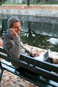 Man writing on netbook and on the phone on a bench outdoors Stock Photos