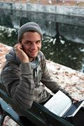 man writing on netbook and on the phone on a bench outdoors - stock photo