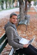 Man sitting on a bench with netbook Stock Photos