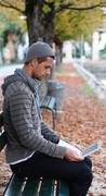 man sitting on a bench with netbook - stock photo