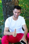 Man sitting under a tree with thumb up Stock Photos