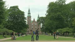 Copenhagen people walk by Rosenborg castle s - stock footage