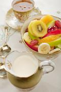 Fresh mixed fruit salad and cream in old crockery Stock Photos