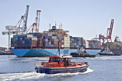 Very large container ship being berthed by two tugs Stock Photos