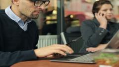 Young businessman with tablet and laptop computer in restaurant, outdoor Stock Footage