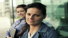 Two smiling businesswoman in front of glass wall, steadycam shot Stock Footage