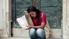 Sad, depressed young woman sitting by the old door, steadicam shot HD - stock footage
