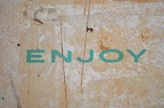 The word Enjoy written in turqoise on old metal Stock Photos